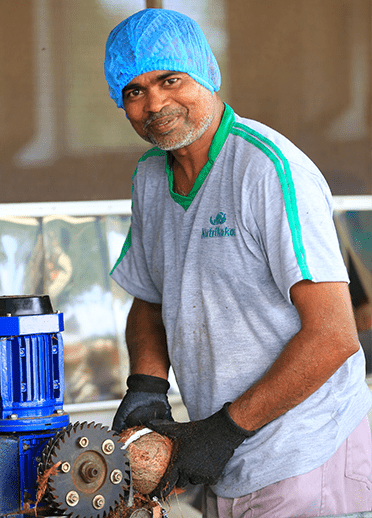 Nutrikokos employee with hair net smiling at the camera while he produces coconut product.